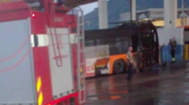 I vigili del fuoco e sullo sfondo il bus incendiato
