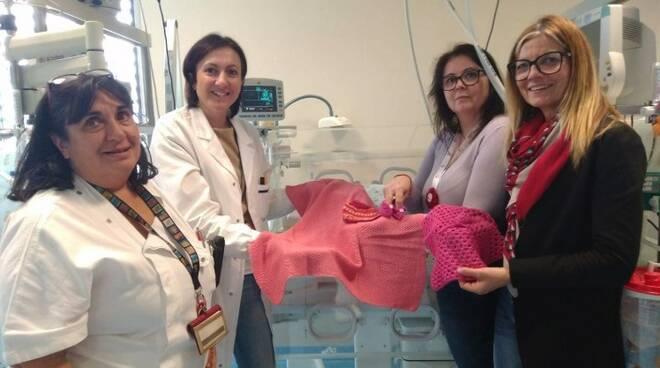 La prima consegna ad un piccolo ospite della subintensiva di Massa e la foto con le infermiere del reparto, la responsabile ostetrica Elisa Bruschi e la coordinatrice infermieristica dell'unità operativa di Pediatria Annunziata Russo
