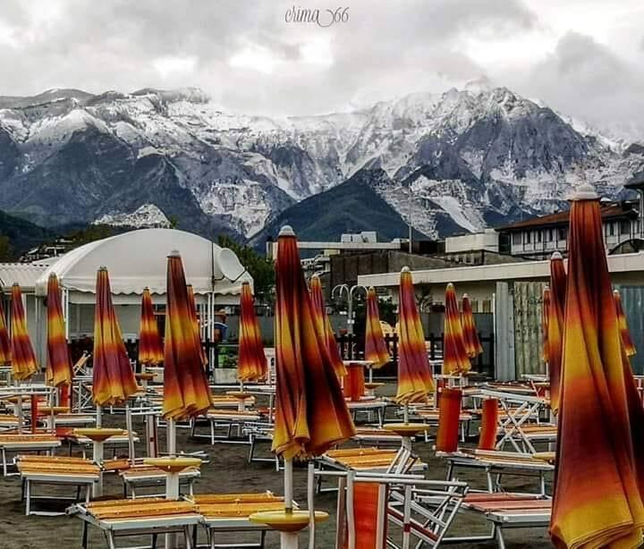 Ombrelloni sulla spiaggia di Marina di Carrara e neve sulle Apuane