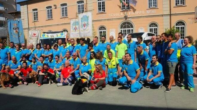 I volontari della Misericordia di Massa e sullo sfondo l'ambulanza donata