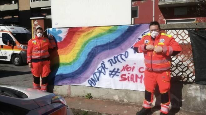 Lo striscione e i volontari della Pubblica Assistenza di Marina di Carrara
